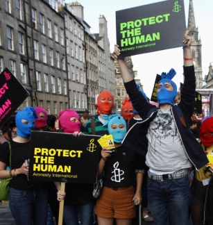 Protesters wearing masks take part in an Amnesty International flash mob demonstration in support of Russian punk band Pussy Riot in the Royal Mile in Edinburgh.(REUTERS / David Moir)