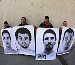 Four men who have each lost an eye due to police rubber bullet attacks show posters of their in juries recently in Barcelona