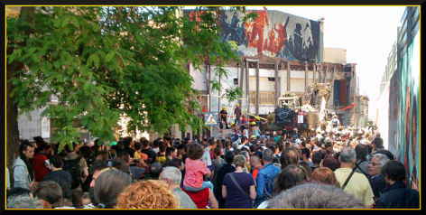 crowds of supporters watch the rebuilding of the anarchist center