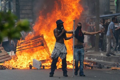 Protesters stand in front of a fire barricade near the aerial metro station of Barbes-Rochechouart, in Paris, on July 19, 2014, during clashes with French riot police in the aftermath of a demonstration, banned by French police, to denounce Israel's military campaign in Gaza and show support to the Palestinian people. Demonstrators threw rocks and bottles at anti-riot squads blocking their route, who responded with tear gas lobbied into the streets. AFP PHOTO / FRANCOIS GUILLOT