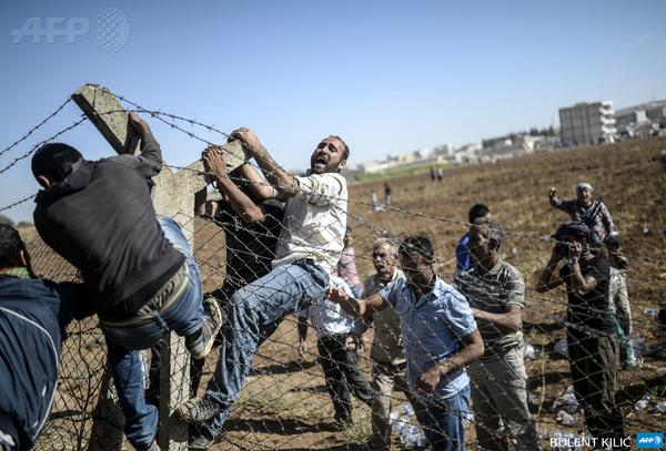 Turkish and Syrian Kurds tear down the border fence to cross into Kobane in neighboring Syria. Photo:AFP