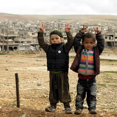 children with destroyed kobane backdrop