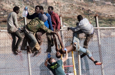An African migrant is lowered down from a border fence by a Spanish Civil Guard as fellow migrants assist, at the border between Morocco and Spain's north African enclave of Melilla during the latest attempt to cross into Spanish territory, April 3, 2014. Spain has more than doubled the strength of security forces at Melilla, after about 500 people stormed its fences in the biggest border rush for years earlier this month. Immigrants from all over Africa regularly dare the razor-wire fences of Spanish enclaves Ceuta and Melilla, which are surrounded by Moroccan territory and sea.