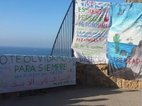 these are the banners in memory of Oussama who died here when he fell from the cliff trying to 'jump a boat' to Europe, the  'Prodein' kids rights group were fined 1500 euros for the action.