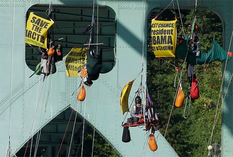 Activists hang from the St. Johns bridge in Portland, Ore., Wednesday, July 29, 2015, to protest  the departure of Royal Dutch Shell PLC icebreaker Fennica, which is in Portland for repairs.  The icebreaker is a vital part of Shell's exploration and spill-response plan off Alaska's northwest coast.  Greenpeace officials say  the activists have enough water and food to last for days, and can hoist themselves to allow other marine traffic to pass. (AP Photo/Don Ryan)