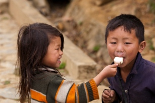 Children sharing ice-cream on stick near Sapa.