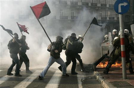 Self-styled anarchists armed with wooden sticks fight against the police in an attempt to release a detained comrade (on the floor) in a cloud of tear gas outside the Greek Parliament in Athens in this February 22, 2007 file photo. REUTERS/Yannis Behrakis/Files