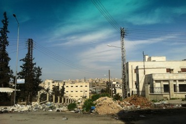 a heap of earth and debris divides the neighborhood of Khalidya, which is under regime control, from adjacent rebel-held Bani Zaid.