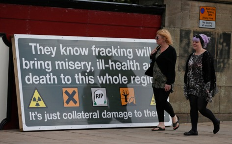 People walk past an anti-fracking poster during a demonstration outside County Hall in Preston, Britain June 23, 2015. Lancashire County Council is debating an application by shale gas firm Cuadrilla Resources to frack on the Fylde coast, local media reported. REUTERS/Phil Noble - RTX1HPFB