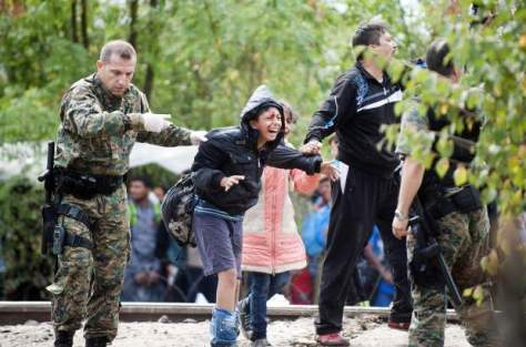 TOPSHOTS A member of the Macedonian police force and a migrant hold an injured boy during a clash between Macedonian police forces and migrant trying to cross an illegal crossing point on the border between Greece and Macedonia near the town of Gevgelija on August 22, 2015. Hundreds of mostly Syrian refugees forced their way over the Macedonian border today as police hurled stun grenades in a failed bid to stop them breaking through, an AFP reporter said. AFP  PHOTO / ROBERT ATANASOVSKIROBERT ATANASOVSKI/AFP/Getty Images