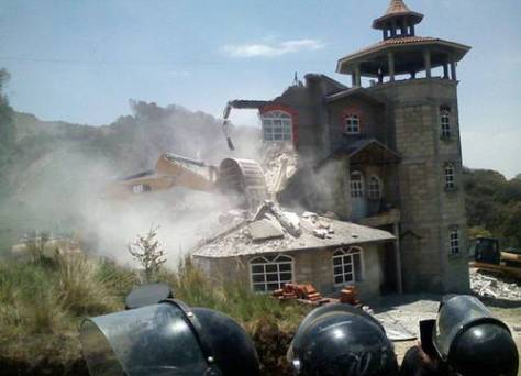 Protected by riot police, construction company's heavy equipment destroys a house in Xochicuautla. Photo: La Jornada