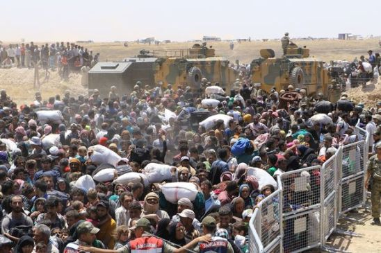 https://thefreeonline.files.wordpress.com/2016/05/syrians-wait-at-the-syrian-side-of-the-turkish-syrian-borderline.