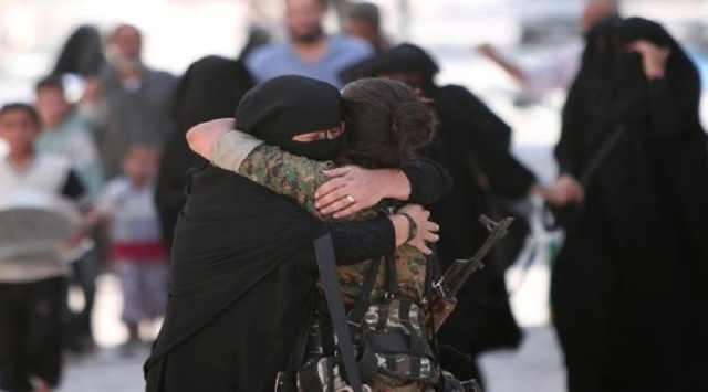 a-woman-embraces-a-syria-democratic-forces-sdf-fighter-after-she-was-evacuated-with-others-by-the-sdf