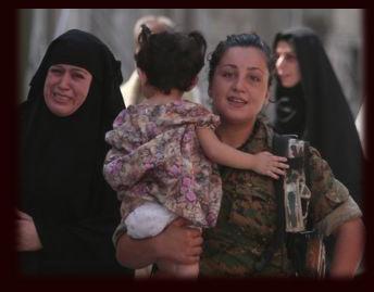A YPJ volunteer helps rescue civilians from ISIS in Manbij.