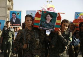 Syrian-Kurdish women carry the coffin of a female fighter in Syria's northeastern city of Qamishli on July 21, 2016 during the funeral of sixteen fighters killed battling the Islamic State (IS) group in Manbij. Thousands of IS soldiers were reported killed in the Manbij battles along with about 150 SDF volunteers, including six from the International Brigade.(William Savage, from the US was killed rescuing civilians).