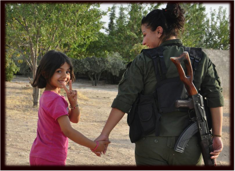 A girl rescued from ISIS terror in Manbij is welcomed by a revolutionary YPJ volunteer.