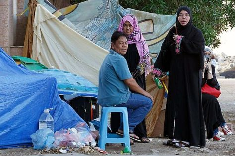 Filipino workers gather near their makeshift tents outside their consulate in the Saudi coastal port city