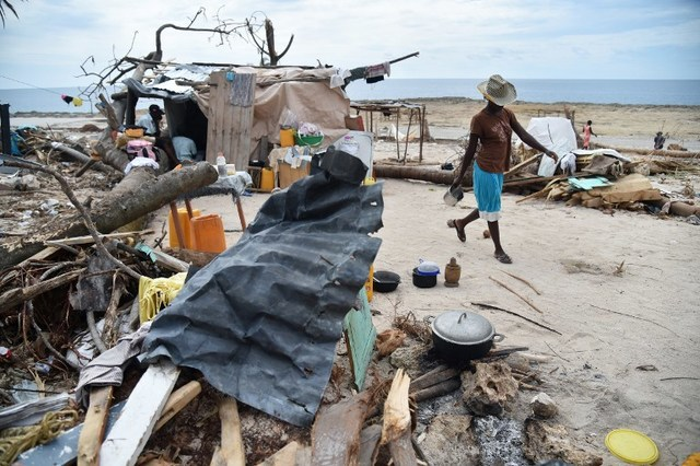 A woman prepares food near her destroyed house in the aftermath of Hurricane Matthew in the commune of Roche-a-Bateaux, southwest Haiti, on October 18, 2016. Food, medicine and other essential aid has been slow to reach areas slammed by Hurricane Matthew. Some desperate Haitians have taken to blocking parts of the road crossing the southern peninsula to intercept humanitarian convoys, in some cases looting them. / AFP PHOTO / HECTOR RETAMAL