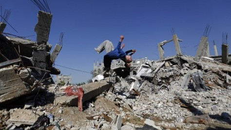 A Palestinian boy practices parkour in the ruins of occupied and blockaded Gaza