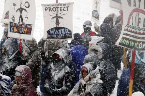"Veterans march with activists near Backwater Bridge just outside of the Oceti Sakowin camp during a snow fall as ""water protectors"" continue to demonstrate against plans to pass the Dakota Access pipeline adjacent to the Standing Rock Indian Reservation, near Cannon Ball, North Dakota, U.S., December 5, 2016.  REUTERS/Lucas Jackson"