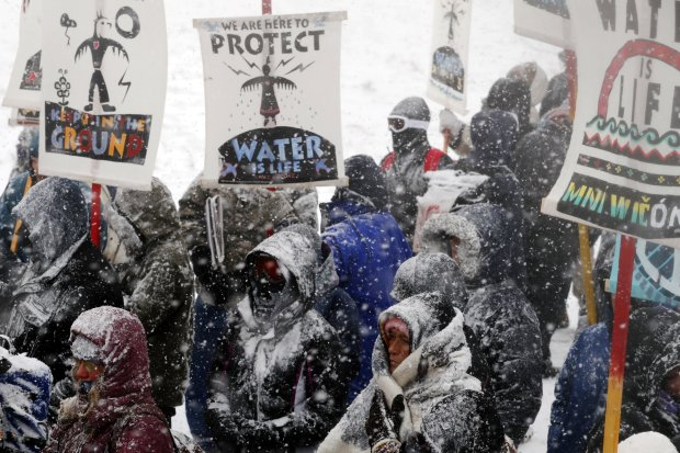 """Veterans march with activists near Backwater Bridge just outside of the Oceti Sakowin camp during a snow fall as """"water protectors"""" continue to demonstrate against plans to pass the Dakota Access pipeline adjacent to the Standing Rock Indian Reservation, near Cannon Ball, North Dakota, U.S., December 5, 2016.  REUTERS/Lucas Jackson"""