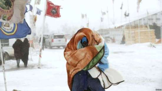 """A camper braces against high winds and a blizzard while walking inside the Oceti Sakowin camp as """"water protectors"""" continue to demonstrate against plans to pass the Dakota Access pipeline adjacent to the Standing Rock Sioux Reservation, near Cannon Ball,"""