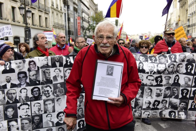 Demonstrators show photographs of Francoism victims during a demonstration in favour of Historical Memory in Madrid on November 22, 2015. Franco came to power after his side won Spain's 1936-39 civil war with the help of Germany's Adolph Hitler and Italy's Benito Mussolini. He then ruled Spain with an iron fist until his death on November 20, 1975. Forty years after the death of Francisco Franco, historians still work to demolish myths that the Spanish dictator spun about himself to hold on to power for decades. AFP PHOTO / JAVIER SORIANO