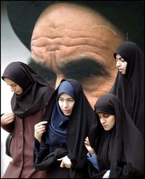 Iranian university students, wearing the Islamic veil, make their way, in front of a picture of late revolutionary founder, Ayatollah Ruhollah Khomeini, inside the campus of Tehran University, in Iran, Sunday, Nov. 9, 2003. Iranian university students marked the first anniversary of a death sentence against one of their professors Sunday by condemning unelected hard-liners and criticizing President Mohammad Khatami's inability to fulfill promises of democratic reforms. Hashem Aghajari, a history professor at Tehran's Teachers Training University was sentenced to death by a court in western Iran last year over charges of insulting Islam and questioning the rule of hard-line clerics. The sentence prompted the biggest student protests in Iran in three years. Iran's Supreme Court lifted the death sentence in February. (AP Photo/Vahid Salemi)